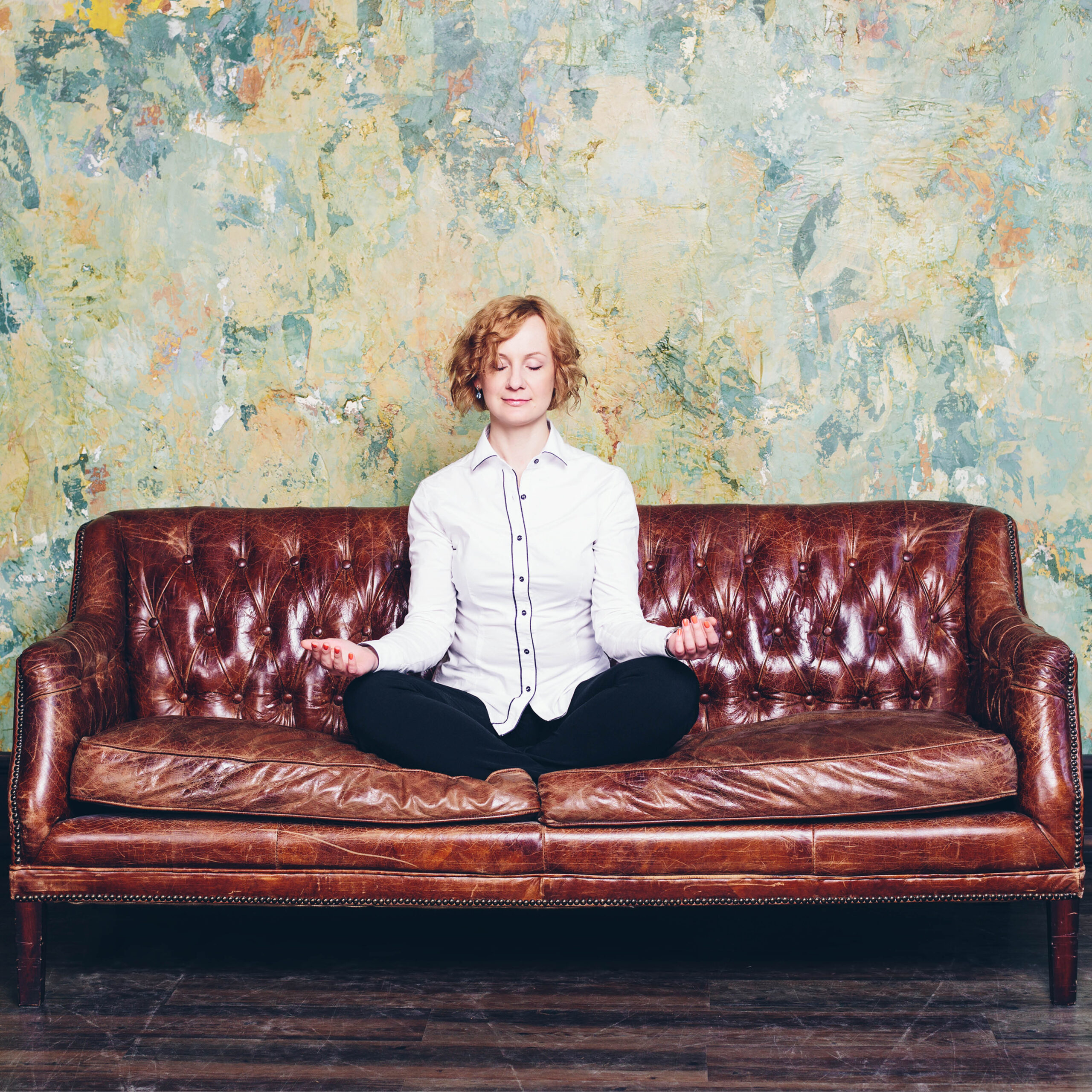 woman meditating on old couch with colourful wall behind